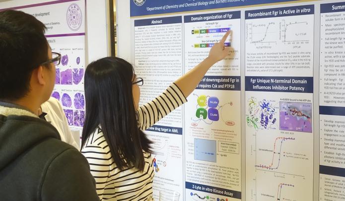 Two Tsinghua University scholars view a poster.