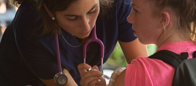 nurse with stethoscope giving a shot to a young patient